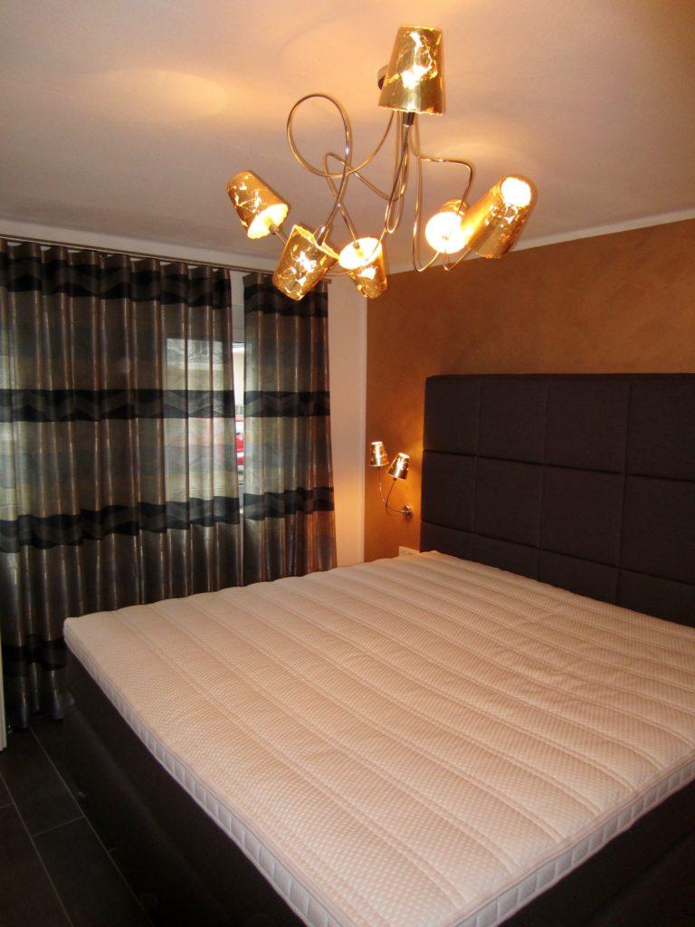 Die Ruheinsel in der Mitte des Schlafzimmers ist ein handgefertigtes Boxspringbett in ganz individuellen Maßen. Passend aufeinander abgestimmt dazu die Wandgestaltung und die Beleuchtung.