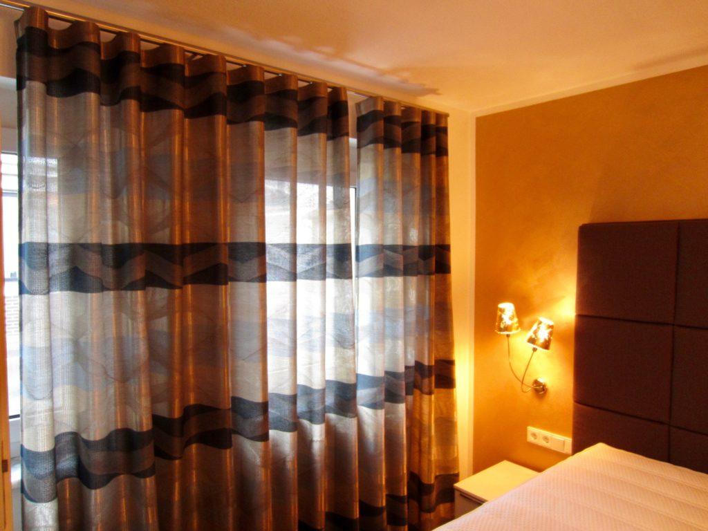 Auch die Vorhänge tauchen den Raum in ein weiches, beruhigendes Licht. Passend abgestimmt zum Beleuchtungskonzept und der goldenen Wandgestaltung.