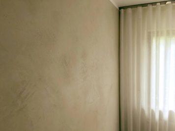 Sonnenschein taucht diese Betonwand in weiches Licht. Unterschiedliche Lichter lassen die Wand in Betonoptik lebendig wirken.