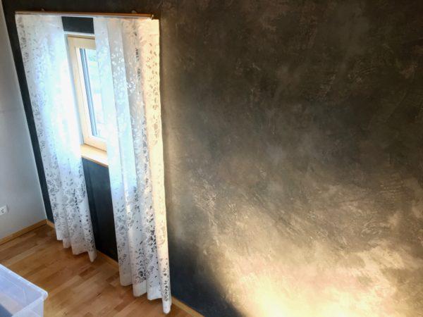 Ein moderner, weißer Wellenvorhang mit einer Edelstahlgarnitur wirkt als belebender Kontrast zur urbanen Spachteltechnik. Beides bildet ins sich einen schönen Kontrast, zusätzlich noch zu dem warmen Holzboden.