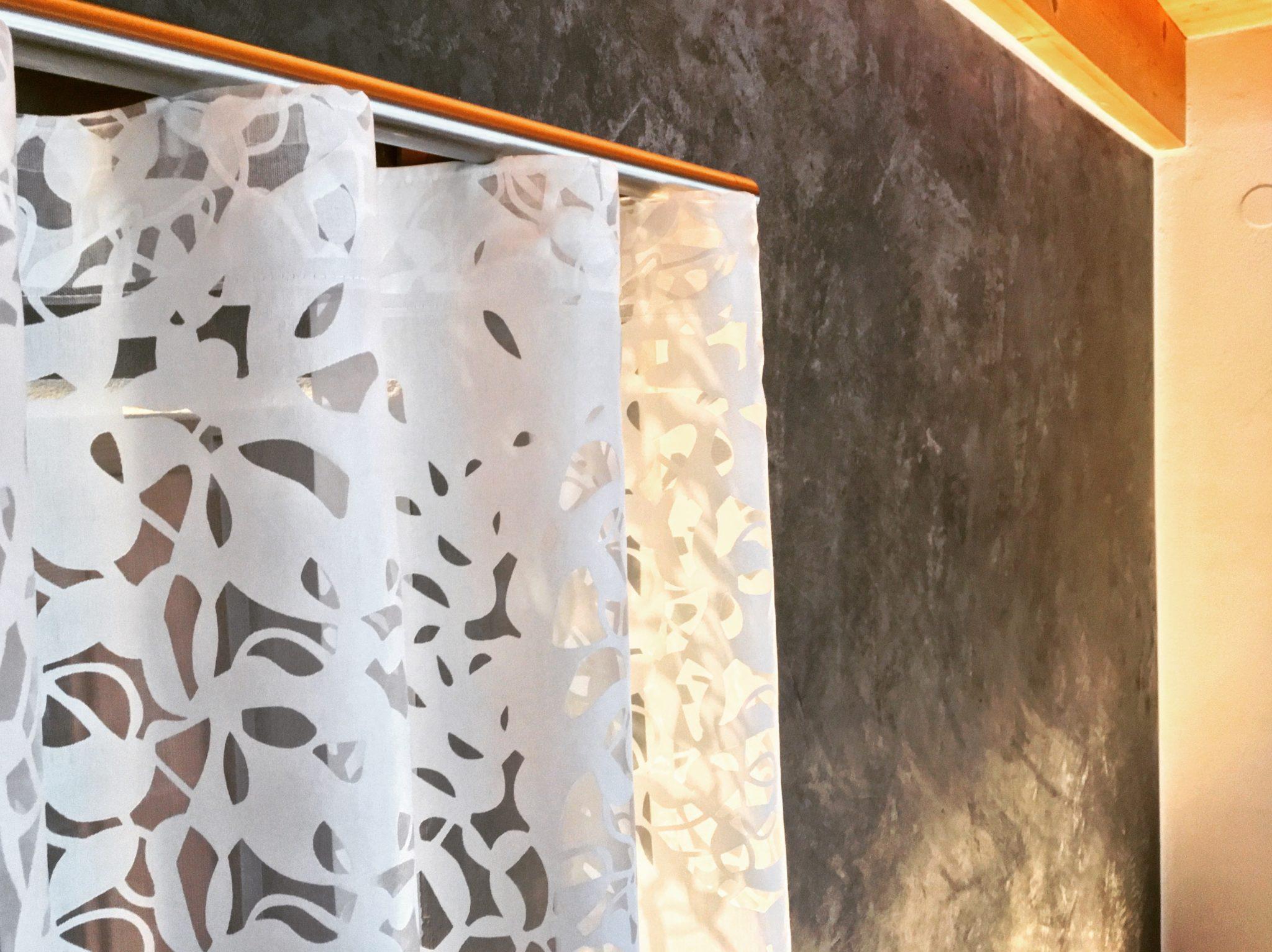 weißer Vorhang als Wellenvorhang mit Edelstahl Vorhangstange auf gespachtelter Wandgestaltung in dunklen Grau