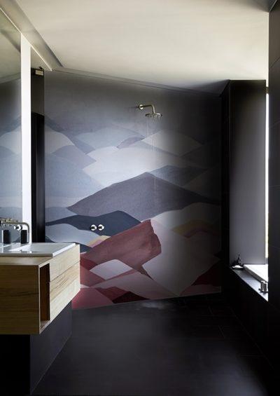 Dunkle Farbgestaltung im Bad ist modern. Die Tapete in der Dusche ein Highlight.