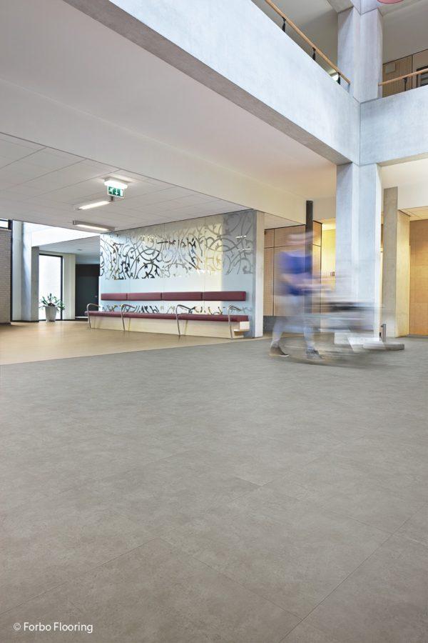 Große, helle Fliesen aus Vinyl. Im Gegensatz zu klassischen Fliesen ist der Bodenbelag viel pflegeleichter und angenehmer an den Füßen.