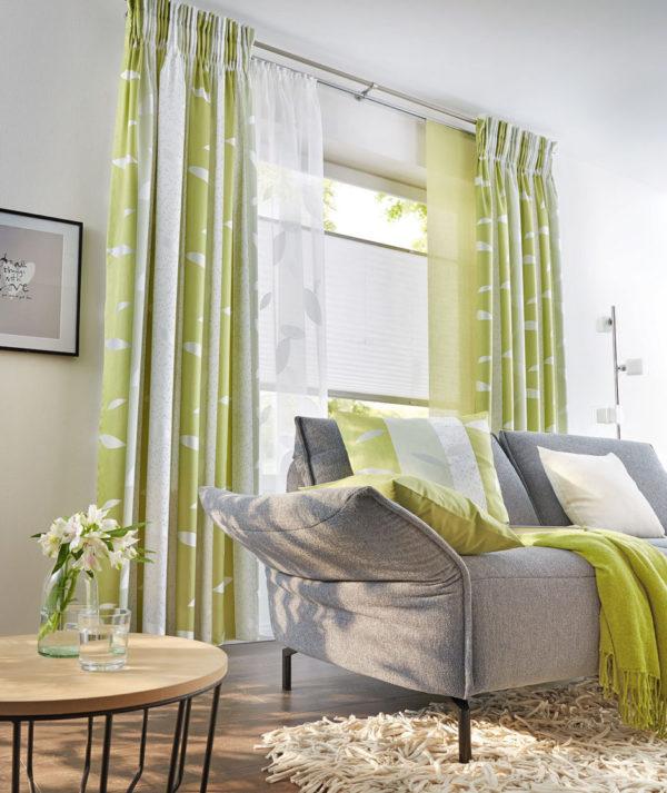 Frische Grüntöne in den Dekoschals, kombiniert mit natürlichen Grautönen und einem luftigen Store.