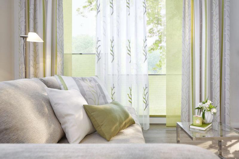 Natürliche Farbekombination von Gardinen, Plissees und Dekoschals. Dazu passend die Kissen auf der Couch.