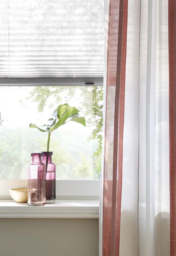 Ein luftiger Stoff als Vorhang kombiniert mit einem Plissee als Sichtschutz im Fenster. Perfekt für moderne Wohnzimmer.